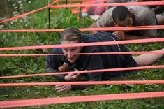 Doing army crawls underneath a low obstacle at the mud run. Here's everything you want to know about Mud Runs!