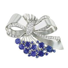 White Gold, Diamond and Sapphire Bow Brooch, J.E. Caldwell   14 kt., the polished white gold ribbons centering a diamond-set panel, edged with diamonds, totaling 54 round diamonds approximately 1.35 cts., supporting a wire spray tipped with 9 round and cushion-cut sapphires approximately 5.50 cts., accented by 10 small round sapphires, signed JE Caldwell, circa 1940, approximately 10.7 dwt.