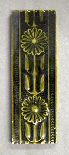 """Craven Dunnill and Co relief moulded dust-pressed tile, vertical running design of a stylized flower on stem, monochrome glazed, 6"""" x 2"""", c1900."""