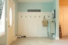 White paneling topped with white crown molding and black storage hooks. Distressed light blue cabinet compliments light blue walls.