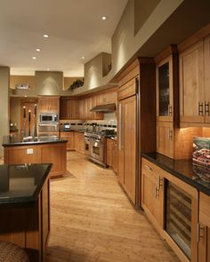 Gourmet kitchen featuring natural cherry wood shaker style cabinets by Wood-Mode. Indian Premium black granite countertops, limestone, granite slab and metal