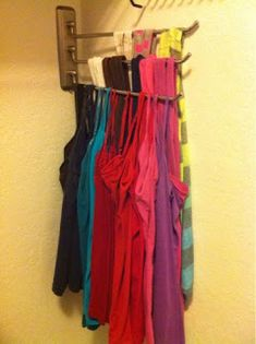 Organize tank tops in your closet with a folding towel holder! Saves tons of space and hangers!!