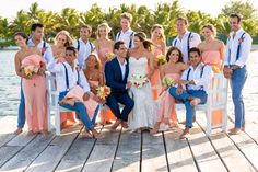 Beach wedding bridal party photo. Groomsmen blue suits and bridesmaids peach dresses #pier #weddingphotos