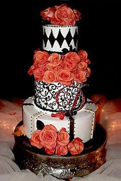 Interesting, three tier black and white wedding cake decorated with orange roses and orange rose wedding cake topper. From www.thepastrystudio.com
