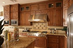 This is the color scheme I want for my kitchen :) Tan granite, medium brown cabinets, light backsplash... Love!!!