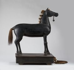 LARGE FOLK ART BLACK-PAINTED HORSE PULL TOY WITH HORSEHAIR MANE AND TAIL AND HARNESS BELL.Sold: $ 3,658.00  Wood figure and platform on wooden wheels. Height overall 31 ½ inches, length 25 ½ inches. Provenance: Edith Gregor Halpert, The Downtown Gallery, New York.