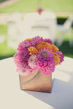 Orange, purple wedding flowers in square vases - Could go low for table arrangements? But tall might fill the space more & create more drama & impact?