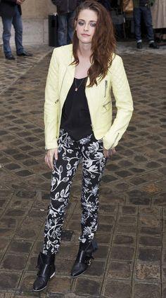 Kristen Stewart è andata alla sfilata di Balenciaga durante la Paris fashion week 2012, con una giacca di pelle neon  giallo limone, con cuciture a trapunta e varie zip, una maglia nera e dei pantaloni stampati con motivo floreale e stivaletti neri.