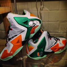 """The University of Miami has been a long time college football powerhouse. Dez Customz pays homage to 'The U' by creating this Nike LeBron 11 """"The U. Cheap Nike Shoes Online, Nike Shoes Outlet, Lebron 11, Nike Lebron, Lebron James, Hurricanes Football, Miami Hurricanes, Air Jordan, Futuristic Shoes"""