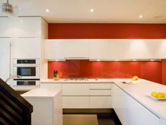 Lacquered white cabinets and quartz countertops pop against a bold crimson backdrop, giving this room a contemporary Asian vibe. The glass backsplash shields the bright wall from wear. Design by Andreas Charalambous