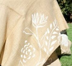 Super cute- burlap with white painted flowers. Table runner?
