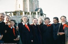 A group of teenage girls gathered in uniform smiling and laughing as they pose for a photo...