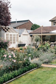 Rear view of period property with lawns and cottage style planting in the borders