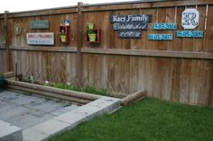 Fence Love - Just because you have a small yard or a plain wooden fence doesn't mean it has to be boring.  I love the way this reader spruced up her backyard with custom homemade signs and shadowbox frames filled with plants.