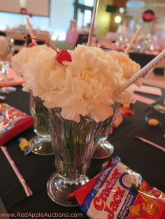 Milkshake centerpieces made from carnation flowers at a school auction Sock Hop theme.  CUTE!