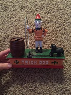 This is a collectable Iron Coin Bank. You put the coin in the dogs mouth and press the button and the dog swings over to the barrel and puts the coin in the bank. Super cute. Rare to find. Make offer.