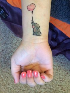 This adorably cute elephant tattoo symbolizes childhood, love and family. Click through to rattatattoo.com to find ideas and inspiration for your own elephant tattoo design.