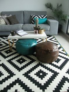 Modern global style living room - moroccan leather poufs, monochrome kilim rug & contemporary grey sofa.