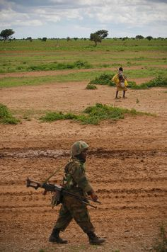 A Somali man walks past a Ugandan soldier serving with the African Union Mission in Somalia (AMISOM) as he patrols a road following an advance on the town of Afgoye to the west of the Somali capital Mogadishu.