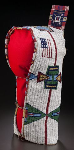 A SIOUX BEADED HIDE BABY CARRIER,    sinew sewn and lane-stitched in green, yellow, white-heart red and two shades of blue beads against a white beaded ground, with a bold design of confronting triangles and American flags, rawhide tab at top, decorated with beaded geometric motifs and hide thongs strung with faceted black glass beads and brass hawk bells