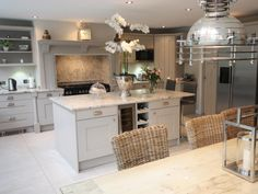Kitchen painted in F&B's Elephant's Breath, granite topped island & worktops, Rangemaster range and chimney breast hood surround, wicker chairs, stone flooring, washed wooden table, industrial task lighting, oversized orchid in ice bucket.