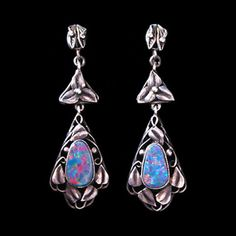 This is not contemporary - image from a gallery of vintage and/or antique objects. RHODA WAGER ( 1875-1953 ) (Attributed)  A pair of Arts and Crafts silver earrings set opals, surrounded by a wirework  frame of leaves.