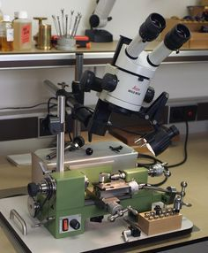 Watchmakers lathe with Lecia stereoscopic microscope. I have considered adding to my lathe a stereoscopic microscope for some operations. The extended handle with a universal coupling connected to the x-direction feed is needed for the close proximity to the tailstock.