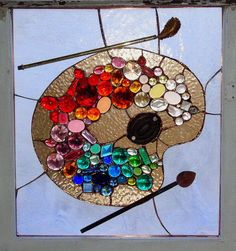 If you use glass beads like river rocks in different colors and hot glue gun them to a saved piece of thick glass you could achieve a similar affect