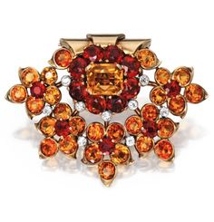 18k Gold, Platinum, Citrine and Diamond Clip-Brooch, Cartier, London The fan-shaped floral cluster set at the top with one emerald-cut citrine, accented by round dark and orange-colored citrines, further set with old European-cut diamonds, signed Cartier, London, numbered 94646, with obscured assay and workshop marks; circa 1945.