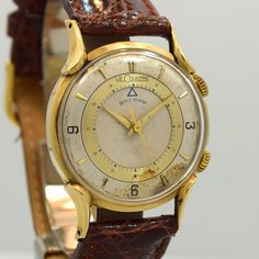 1950's Vintage Jaeger Le Coultre Memovox Wrist Alarm 14k Yellow Gold watch with Original Patina Silver and Gold Dial with Arabic 3, 6, and 9 with Elongated Applied Gold Markers. Triple Signed. Swiss C