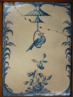 Acc. kat: Kakelplatta, dekorerad med konturen med gungande fågel, blommor och blad i blått.    Har hört till en kakelugn i gården S. Kungsgatan 23. Gävle.    Beskrivning 2007: Kakelplatta, dekorerad i blått och vitt. Gungande fågel i ring, blommor och blad.