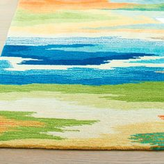 Roll out our exclusive, Hand-tufted Watercolor Rug, and you'll discover the real beauty is in the eye of the beholder. Variegated brushstrokes of blue,    orange, and green hues evoke images of the sea and sky, but what you see is entirely personal. Though one thing is certain-this area rug is magnificently    dramatic and colorful any way you look at it. Exquisite detailing and shading is created through intricate color blending techniques.            Area rug with a multi-hued water...