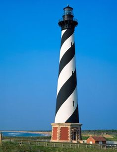 An iconic symbol of North Carolina's Outer Banks, the Cape Hatteras Light is the tallest lighthouse in the United States and one of the tallest in the world. Cape Hatteras Lighthouse, Lighthouse Photos, Beacon Of Light, Out To Sea, Water Tower, Architectural Digest, Vacation Spots, Beautiful Places, United States