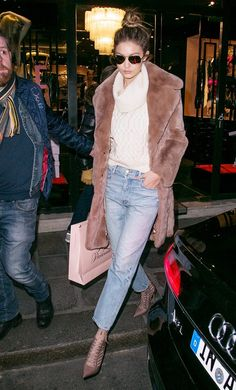 Gigi Hadid wears a cowl-neck sweater, fur coat, cropped jeans, lace-up pumps, and aviator sunglasses