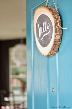 fun alternative to a wreath, a log slice with chalkboard paint.