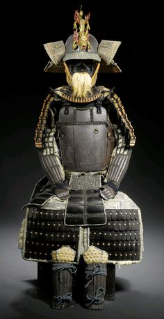 Composite Gusoku by Myochin Nobuiye and Myochin Shikibu Muneakira. Late Muromachi and Edo Period, early 16th and 18th century. Helmet signed Myochin Nobuiye, do signed Myochin Shikibu Muneakira,  Sixty two plate russet iron suji bachi with a tosei mabisashi covered in sakura gawa The tatami do of russet iron plates joined by mail, the three main front plates riveted together and engraved with Fudo and his two acolytes Kongara Doji and Seitaka Doji, on the upper right is a tameshi bullet…