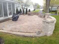 Paver patio with sitting wall and fire pit under construction.
