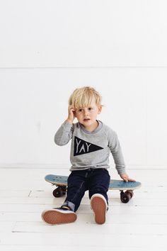 Little boy on a skateboard. Cute pennant flag sweatshirt.