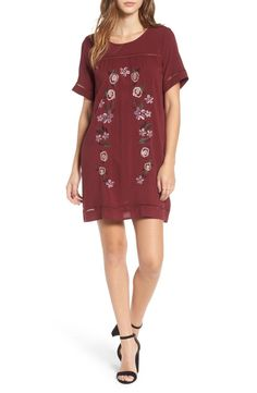 A wreath of embroidered flowers adds sweet, boho style to this breezy dress trimmed with sheer ladder stitching.