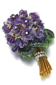 Amethyst, nephrite and diamond brooch, 1960s Designed as a bouquet of violets, with carved amethyst flowers accented with brilliant- and single-cut diamonds and carved nephrite leaves, one leaf and flower deficient.
