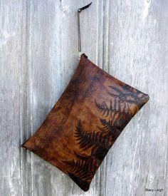 Leather clutch bag made from a very unique, earthy leather that is embossed with ferns and a wood grain pattern. The bag is 16 wide by 11 tall. It is