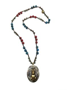 """Rabbits are symbolic of creativity. Handmade soldered pendant hangs from this unique crocheted necklace made with pyrite, ocean jasper, and red magnesite beads. Loop and button closure. 23"""" long, pendant 2"""""""