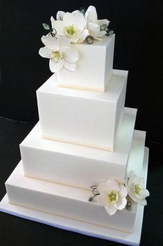 Tiers of traditional white cake are decked with ivory flourishes, satin ribbon and fresh white and pink roses.