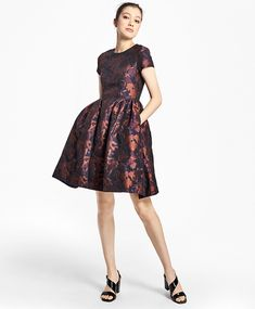 """Crafted from a cotton-blend fabric woven in Italy, this fully lined short-sleeve dress has a fit-and-flare silhouette, a luxurious floral jacquard brocade fabric, an elegant jewel neckline, a flattering empire waist with a classic dirndl-style skirt, and a back zip closure.<br><br>38""""; dry-clean only; woven in Italy; made in Portugal."""