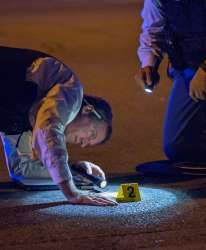 Members of the Chicago Police Department look at an evidence marker - Erin…