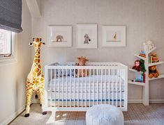 Chic boy's nursery features an accent wall clad in gray faux bois Wallpaper, Schumacher Faux Bois Wallpaper, lined with a collection of baby animal art from The Animal Print Shop over a white Oeuf Sparrow Crib dressed in blue elephant bedding flanked by a Melissa & Doug Plush Giraffe to the left and a Babyletto Spruce Tree Bookcase to the right.