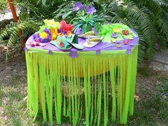 Mesa con flecos hawaianos, muchas flores y sandalias de regalos para tus invitados. #fiestahawaiana #fiestas #ideasparafiestas
