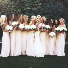 bride next to bridesmaids in long light pink dresses holding gorgeous white bouquets with green leaves underneath