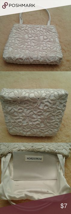 """Nordstrom cream evening bag This is a small cream evening bag in gently used condition. It is satin lined with a small pocket and a magnetic snap closure. It is heavily embroidered all over with petalled flowers with rhinestine centers and connected by vines. It measures 6""""x8""""x2 1/4"""". The 2 satin straps have a 6"""" drop. Note: The bag is in great condition on the outside, but has some marks on the lining at the bottom (see pic 3). Nordstrom Bags Mini Bags"""