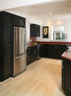 Love the Maple hardwood flooring with the black cabinets and stainless appliances.  Great use of the countertops to bring in another color!